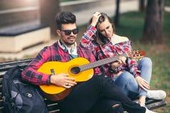 Pares felices en el parque que toca la guitarra Imagenes de archivo