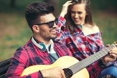 Pares felices en el parque que toca la guitarra Foto de archivo