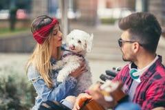 Pares felices en el parque que toca la guitarra Imágenes de archivo libres de regalías