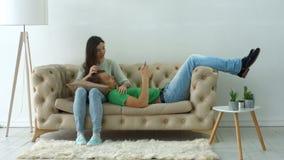 Pares felices en el sofá que disfruta de ocio en casa almacen de video