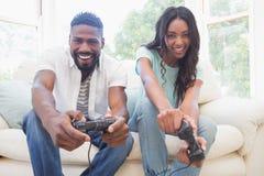 Pares felices en el sofá que juega a los videojuegos Foto de archivo