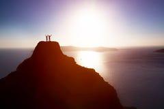 Pares felices en el top de la montaña sobre el océano que celebra la vida, éxito Imagenes de archivo