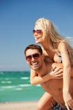 pares felices en gafas de sol en la playa Imagen de archivo libre de regalías