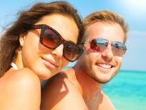 Pares felices en gafas de sol en la playa foto de archivo