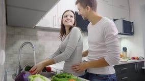 Pares felices en la cocina que cocina junto almacen de video