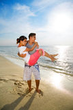 Pares felices en la playa Foto de archivo