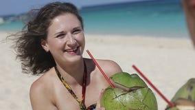 Pares felices en la playa con el coco metrajes