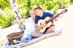 Pares felices en la playa con la guitarra Fotos de archivo libres de regalías