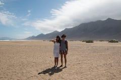 Pares felices en la playa de Cofete, Fuerteventura Tiro ancho con el fondo escénico Imagen de archivo
