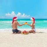 Pares felices en la playa en los sombreros de santa que hacen los presentes para el christma Imágenes de archivo libres de regalías