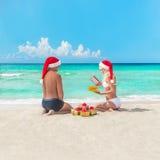 Pares felices en la playa en los sombreros de santa que hacen los presentes para el christma Imagenes de archivo