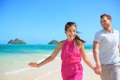 Pares felices en la playa que corre divirtiéndose en Hawaii Fotografía de archivo libre de regalías
