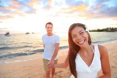 Pares felices en la playa que lleva a cabo las manos en la puesta del sol Imagenes de archivo