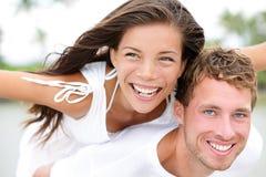 Pares felices en la playa que tiene transporte por ferrocarril de la diversión en amor Foto de archivo libre de regalías