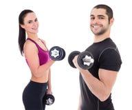 Pares felices en la ropa de deportes que hace ejercicios con el isolat de las pesas de gimnasia Foto de archivo libre de regalías