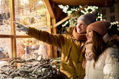 Pares felices en la ventana de la tienda del mercado de la Navidad Fotografía de archivo
