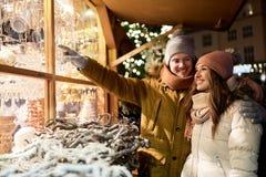 Pares felices en la ventana de la tienda del mercado de la Navidad Fotos de archivo libres de regalías
