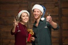Pares felices en los sombreros de Papá Noel con los vidrios de shampagne Imagenes de archivo