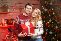 Pares felices en los suéteres del invierno que sonríen y que sostienen la caja de regalo roja grande Fotografía de archivo libre de regalías