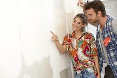 Pares felices en nueva casa bajo construcción foto de archivo