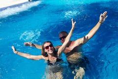 Pares felices en piscina imagen de archivo