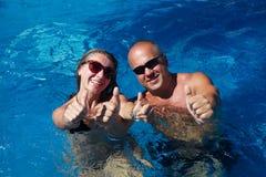 Pares felices en piscina fotos de archivo