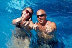 Pares felices en piscina imagenes de archivo