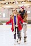 Pares felices en pista de patinaje Imagenes de archivo