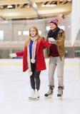 Pares felices en pista de patinaje Fotos de archivo