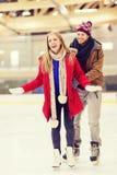 Pares felices en pista de patinaje Fotografía de archivo