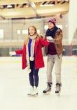 Pares felices en pista de patinaje Foto de archivo