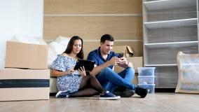 Pares felices en su nuevo plano que busca los nuevos muebles en línea metrajes