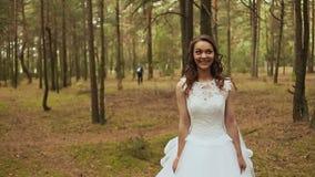 Pares felices en un bosque en el aire fresco El novio va a la novia con un ramo hermoso La novia todavía de pie almacen de video