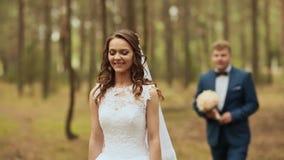 Pares felices en un bosque en el aire fresco El novio va a la novia con un ramo hermoso La novia todavía de pie almacen de metraje de vídeo