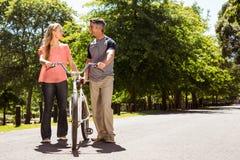 Pares felices en un paseo de la bici Imagenes de archivo