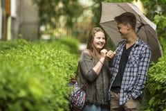 Pares felices en un paseo en el parque con el paraguas Imagen de archivo libre de regalías