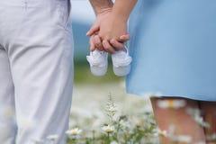 Pares felices en un prado entre las flores Fotos de archivo libres de regalías
