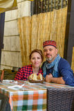 Pares felices en un restaurante al aire libre del vintage Havin de dos turistas imagen de archivo libre de regalías