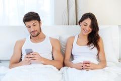 Pares felices en una cama con los teléfonos móviles Fotos de archivo libres de regalías