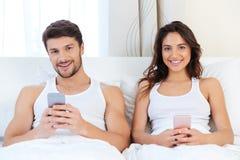 Pares felices en una cama con los teléfonos móviles Foto de archivo