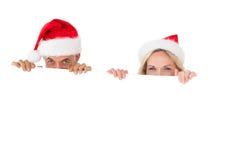 Pares felices festivos que sostienen el cartel grande Foto de archivo libre de regalías