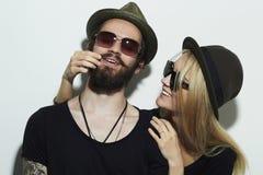 Pares felices hermosos en el sombrero que lleva los vidrios de moda juntos Imagenes de archivo