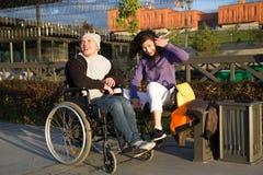 Pares felices - hombre discapacitado en silla de ruedas que habla con la mujer joven atractiva enjoing la puesta del sol foto de archivo
