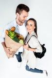 Pares felices jovenes con el bolso de ultramarinos en blanco Fotografía de archivo libre de regalías