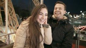 Pares felices jovenes el fecha en Luna Park Los amantes en el tiovivo son felices almacen de metraje de vídeo