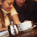 Pares felices jovenes en café, visión a través de una ventana Imagen de archivo libre de regalías