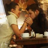 Pares felices jovenes en café, visión a través de una ventana Foto de archivo libre de regalías