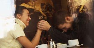 Pares felices jovenes en café, visión a través de una ventana Imágenes de archivo libres de regalías