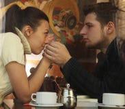 Pares felices jovenes en café, visión a través de una ventana Fotos de archivo libres de regalías