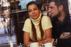 Pares felices jovenes en café, visión a través de una ventana, primer Imágenes de archivo libres de regalías